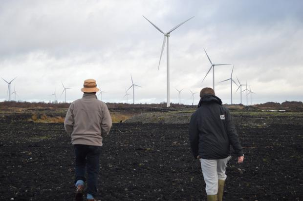 Jody Corcoran, with son Vincent, approaching wind turbines at Mount Lucas bog in Offaly. Photo: Joe Corcoran