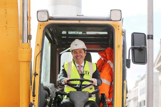 Transport Minister Paschal Donohoe gets to grips with a mini-excavator at the start of the main Luas Cross City track laying works on Dublin's O'Connell Street yesterday