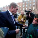 Taoiseach Enda Kenny talking to Martin Naughton from Dublin who was protesting outside Leinster House yesterday. The protest was in aid of people with disabilities and was organised by the AT Network. It has criticised spending cuts made by the government to services in recent years