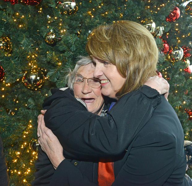 Tanaiste and Labour Leader Joan Burton (right) hugs Rose McKinney (age 77 from Cabra) during a visit to the 'I Believe' Christmas Village in Dublin