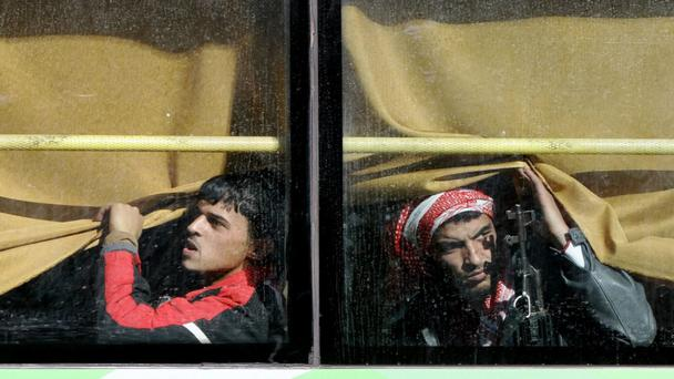 Syrian rebel fighters stare cautiously out of their bus window as hundreds were evacuated under ceasefire from the last rebel-held district
