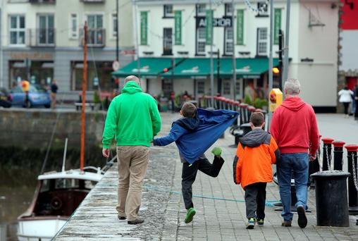 Gay couple Donal Traynor (left) walks with his partner Joseph Bowlby and their adopted sons at their home in Dungarvan