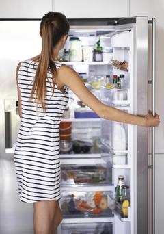 A young woman looking for something in her refrigerator