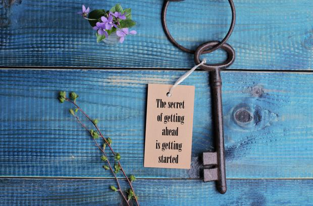 The secret of going ahead is getting started quotation. Life, success concept. Vintage key on wooden background