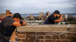 Members of the NYPD specialised unit on watch from a rooftop on Coney Island. Photo: Mark Condren
