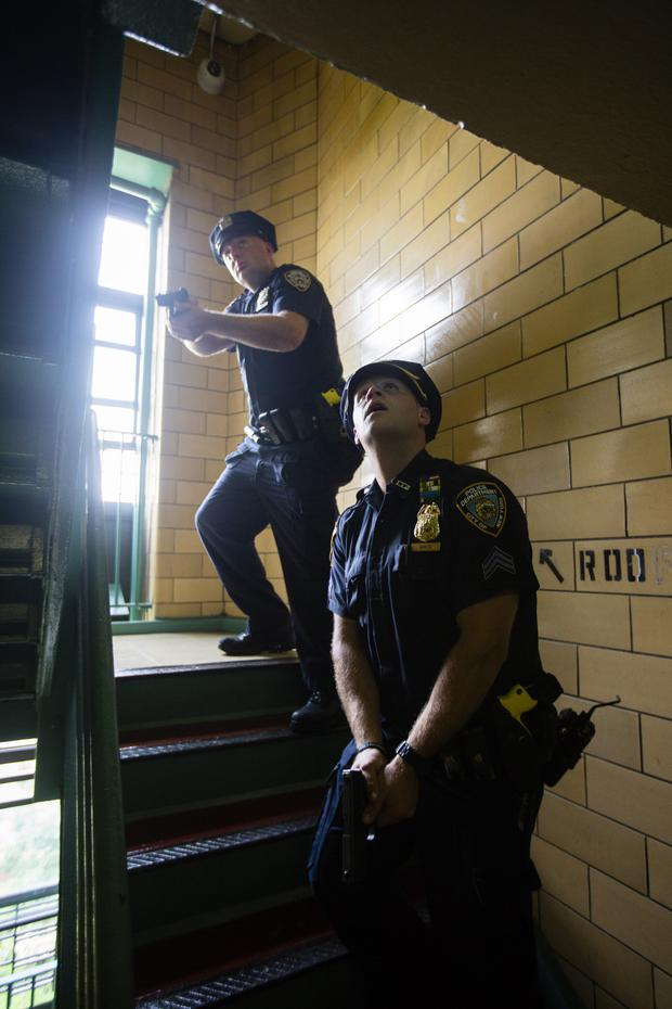 NYPD officers clear a stairwell before entering a rooftop of a housing project. Photo: Mark Condren