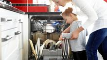 Young mother and her son loading a dishwasher in the kitchen