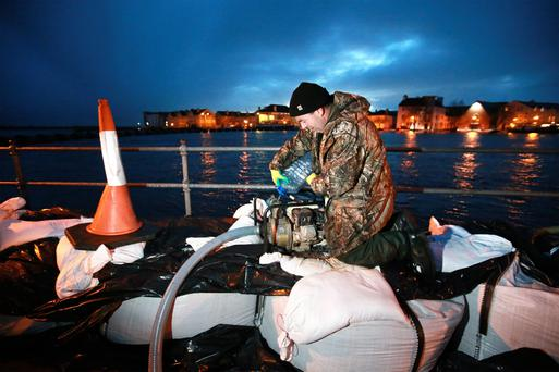 Kevin 'Boxer' Moran with a pump helping to stop the floods from entering homes at The Strand in Athlone