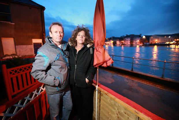 Séamus Meade and Regina Schaub, owners of the Shannon Crafts and Coffee Dock, beside the rising Shannon at the Strand in Athlone