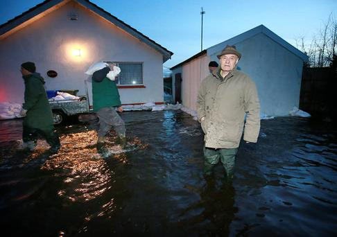 Paddy Kavanagh stands in his front garden as volunteers place sandbags around his house in Golden Island, Athlone