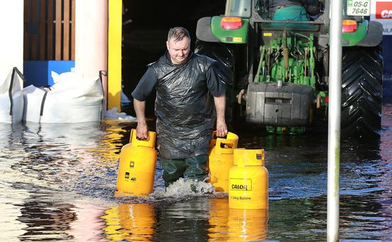 Peter Madden carries some gas cylinders through the floodwaters in Ballinasloe, Co Galway