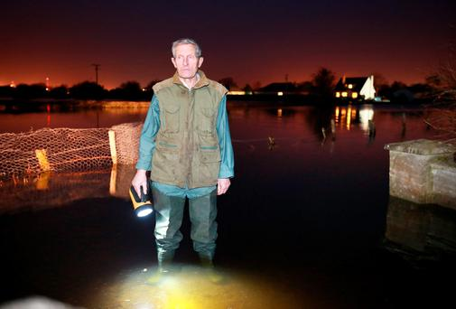 Farmer Michael Macken pictured standing with at the entrance to this farm yard which is surrounded by the River Shannon floodwaters at Carrickobrien near Athlone.