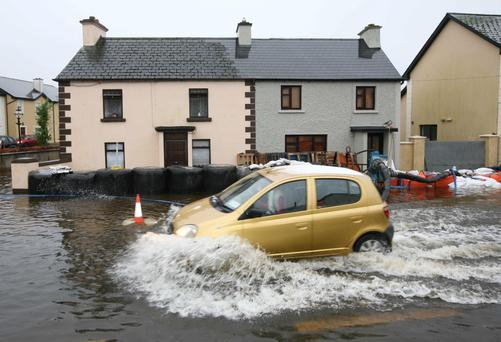 A car drives through a flood where bales of silage were used in an effort to limit the damage to houses in Leitrim Village