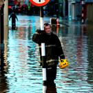 A member of the fire service takes a short break as flooding continues in Bandon, Co. Cork, following storm Frank. Photo: Brian Lawless/PA Wire
