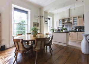 The kitchen/dining area is on the upper floor of the villa-style house, so there's plenty of light. The modern units and the 19th-Century round table work well together. The tall, thin bronze sculpture depicting a man holding two buckets, titled 'The Balance of Life', is by Patrick O'Reilly
