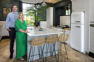 Sinead Gunnigle and her husband, Guy Palmer, in the kitchen. As a stark contrast to the ultra sleek units and island, Sinead has dramatic wallpaper from the House of Hackney, giant ferns and a mirror over the Aga. The parquet-effect flooring is actually tiling. Photo: Tony Gavin