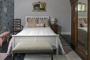 """The guest bedroom is sparsely furnished compared to the exuberance of the rest of the house but has a wallpapered feature wall. """"I love wallpaper company House of Hackney so much, I want to become their representative in Ireland,"""" Sinead says"""