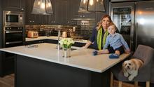 """Lynn Pitcher, owner of Source Interiors, Swords, in her kitchen with her son, Shay, and her dog, Susie. The units are covered in an anthracite shade.  """"I love the warmth of dark shades, and as the house is south-facing, there's a lot of light, so it's never too dark,"""" she says. Photo: Tony Gavin"""