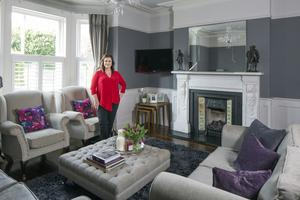 Novelist Jane Ryan in her period living room, which is decorated in shades of grey and purple. The armchairs are from her childhood home; she had them reconditioned and covered. Photo: Tony Gavin