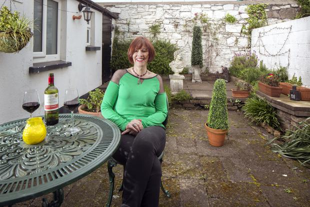 """Eleanor in the back garden of her home in Dublin 8 - a stone's throw from town. """"I love my bike and my home is near everywhere [in the city] so I can just hop on the bike,"""" she says. The bust is of Apollo"""