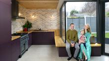 Eoin and Kate with their delightful daughter, Evie, in the kitchen area. Light pours in through the angled windows, and the area just outside the window is full of colourful plants in summer, giving the couple the sense of the outside/inside, which Kate wanted as a result of her years living in New Zealand
