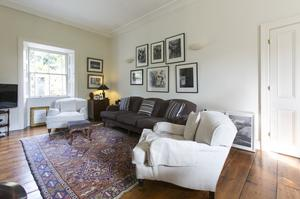 This light-filled sitting room is off the kitchen/dining area. The many framed photos include works by Bono and the Edge. Some are gifts, and Chantal bought some at auction. Photo: Kip Carroll