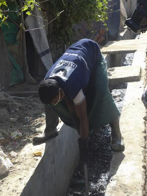 A volunteer supports Oxfam's sanitation programme, ensuring the people in the camp have clean water, safe sanitation and are kept safe from deadly disease