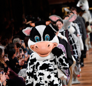 A cow mascot leads out models at Stella McCartney show. Photo: AFP via Getty Images