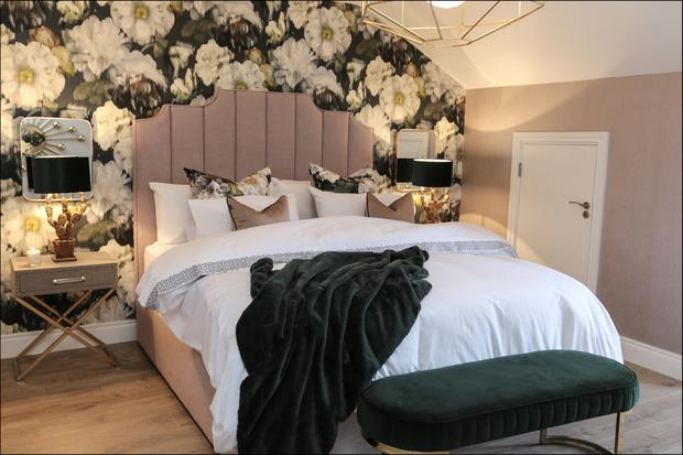 Erin's bedroom is green and blush pink, with one wall featuring a botanical print. The headboard and base are covered in textured linen