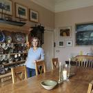 Bridget in her dining room. The dresser is from the Wicklow house and is lined with pieces picked up by her mother, Nancy Wynne-Jones.