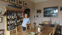 """Bridget in her dining room. The dresser is from the Wicklow house and is lined with pieces picked up by her mother, Nancy Wynne-Jones. """"She travelled a lot and brought pieces back from everywhere,"""" Bridget says. Her father, Conor Fallon, bought her the chairs. """"I had just split up with my boyfriend and moved flat, and he bought the chairs and had them sent to me; he was so sweet"""". Photo: Tony Gavin"""