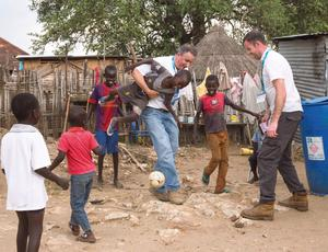 Managing Director of Fyffes Ireland Gerry Cunningham and journalist Jason O'Brien play a game of football with local children in Juba. Photo: Mark Condren