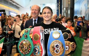 Shane Ross lingers behind Katie Taylor as she returns home to Dublin Airport. Photo: Frank McGrath