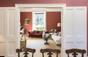 Double doors open from the formal dining room to another living room. The red sofa is a 19th-Century Chesterfield and the chairs dating from the same period are known as library tub chairs