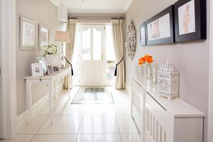 The front door was what seduced Anne Marie Hamill when she first saw the house. The hall is also very charming, with its white colour scheme, Crema Marfil flooring and walls lined with photos of Anne Marie's daughters
