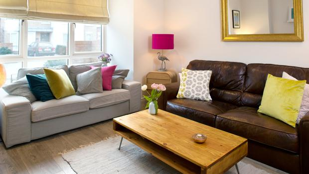 Caroline Foran's living room, where she likes to use neutral basics but pops of colour in disposable items like cushions. The flamingo lamp is by Rachel McCann, whose work is stocked at Detail in Arnotts