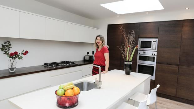 "The entrepreneur in her kitchen. She opted for white units with dark-wood countertops and white quartz on the island. ""Mum has the same colour scheme. John Rocha is married to my Aunt Odette, and he went to Mum's house and he advised her to do whites and creams and dark wood, and I copied her,"" says Sophie. The black vase is a John Rocha design. Photo: David Conachy"