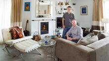 Diego and Evan in the living area. They installed the smoked-oak flooring, and the fireplace, which they bought in Hearth and Home. They brought the spear back from a trip to Indonesia. The couple collect designer furniture, such as the Barcelona chair and the Eileen Gray table