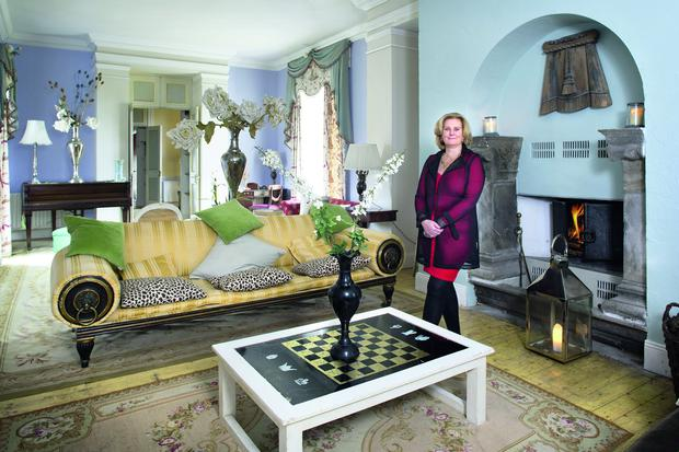 Emily Naper in her drawing room, which is full of antique rugs and clever finds, as well as objects she made herself, including mirrors and frames. 'I wanted to be an artist, but I never had the time,' she reveals
