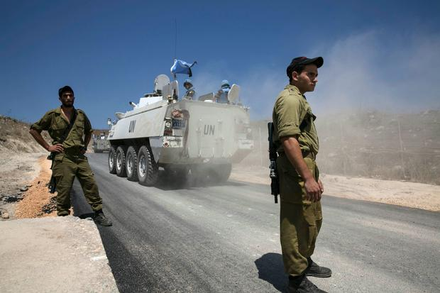 Members of the United Nations Disengagement Observer Force (UNDOF) ride armoured personnel carriers (APCs) past Israel soldiers in the Israeli-occupied Golan Heights
