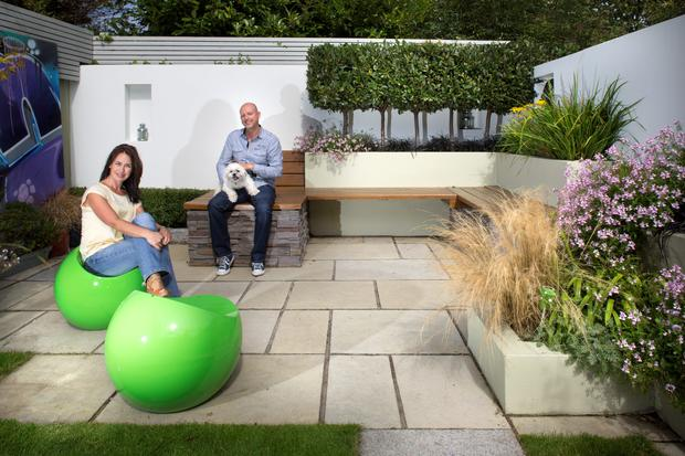 Garden designer Kevin Dennis with his wife Annette and Chip, their shih-tzu. The seating is iroko and the planting includes box, bay and olive trees.The compact garden includes a climbing frame for the couple's two children. The green seats are by Irish designer Finn Stone and the graffiti is one of 25 panels used by Kevin in his award-winning Bloom design.