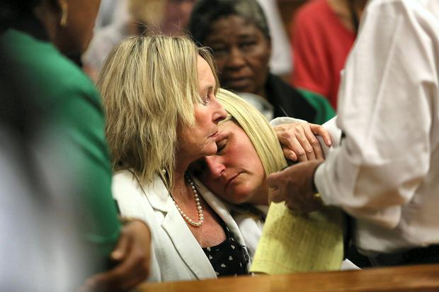 June Steenkamp comforts Kim Martin, Reeva's cousin, in court.