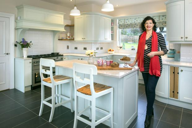 Eleanor Hickson in the kitchen of her new home. The floor is covered in slate tiles and the units were made up by Wexford-based Darren Langrell. The units have curved edges as Eleanor is not a straight-line sort of person. The worktops are camino quartz, and the retro lights are from Ikea