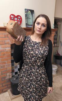 Joanna Kiernan holding the brick which was used to break into her home