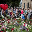 People lay down flowers outside the cathedral in Oslo July 22, 2012, on the one year anniversary of the twin Oslo-Utoeya massacre by self confessed killer Anders Behring Breivik