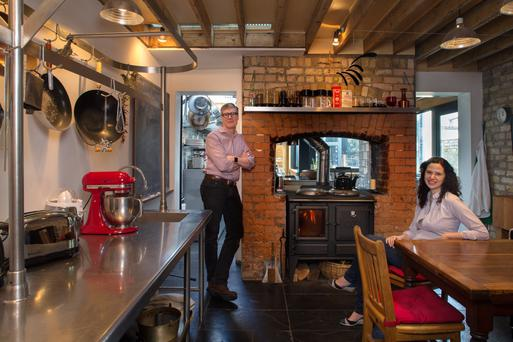 Artist Paul Gregg and his wife Lucia in the inner kitchen which is an unusual mixture of exposed beams, bricks and stainless steet. Photo: Tony Gavin.