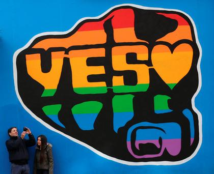 Members of the public beside a mural in Dublin's Temple Bar area by street artist SUMS supporting a yes vote in the forthcoming Gay Marriage referendum in Ireland
