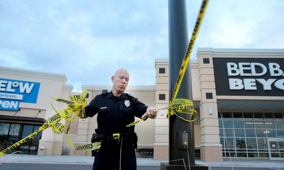 A Waco policeman takes down crime scene tape as officers reopen Central Texas Market Place after Sunday's shooting in the Texan town. Photo: Jerry Larson