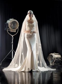 'Heidi' silk-satin, low-back, fishtail gown, with lace-trimmed train and sculpted upper body in French lace, €3,850; cap-veil, embroidered with lace flowers and beaded lace, €795; silk-flower bouquet, €150, all House of Delphine