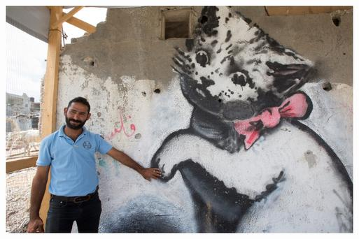 Symbol of life: Father-of-six, Mohamed al Shanbari (30) with his Banksy, which appeared on a wall of his destroyed home in February